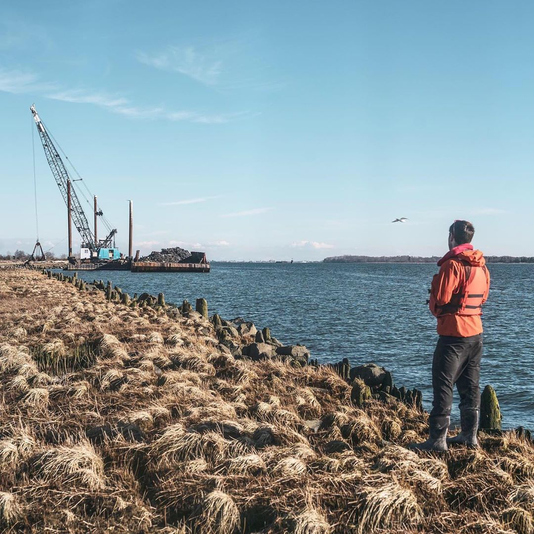 Raincoast scientist in red jacket watches crane work from the shore