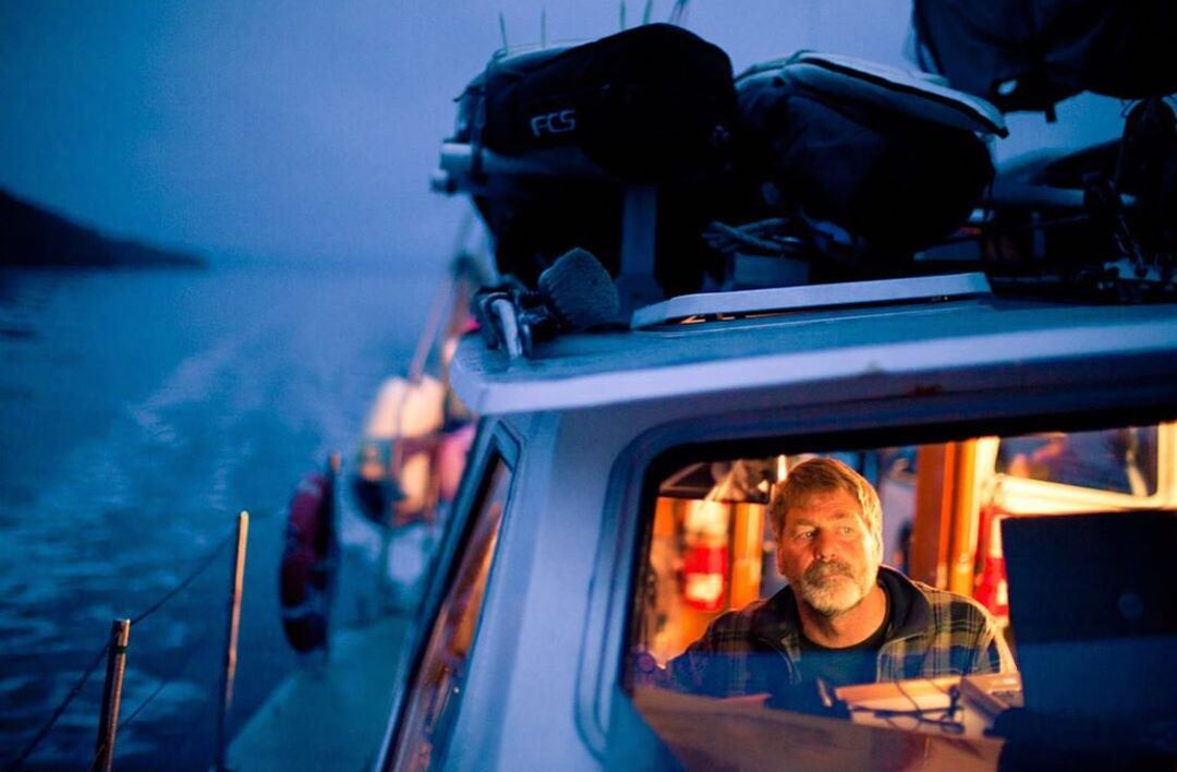 Raincoast guide Brian Falconer visible in the cockpit of a boat lit blue in the dusk with ocean and dark cliff in the background