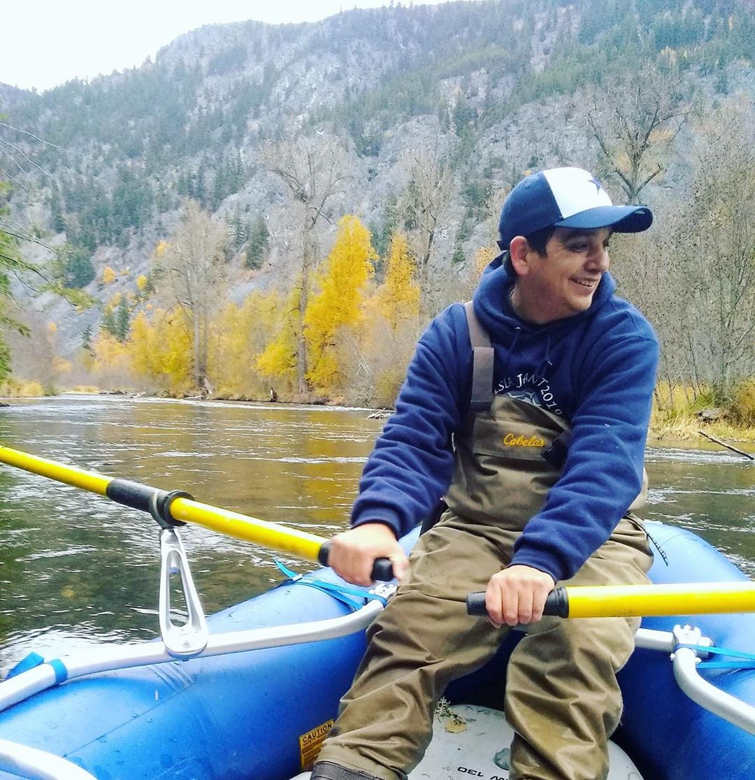 Scientist in a white and blue baseball cap and blue shirt with khaki overalls holds and rows two paddles, rowing a blue dinghy in the water.