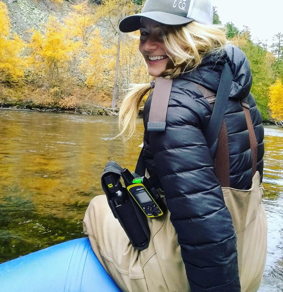 Scientist with long blonde hair tucked under a grey baseball cap, wearing a puffy dark blue jacket stands on the edge of water carrying some equipment and turning around to smile at camera.