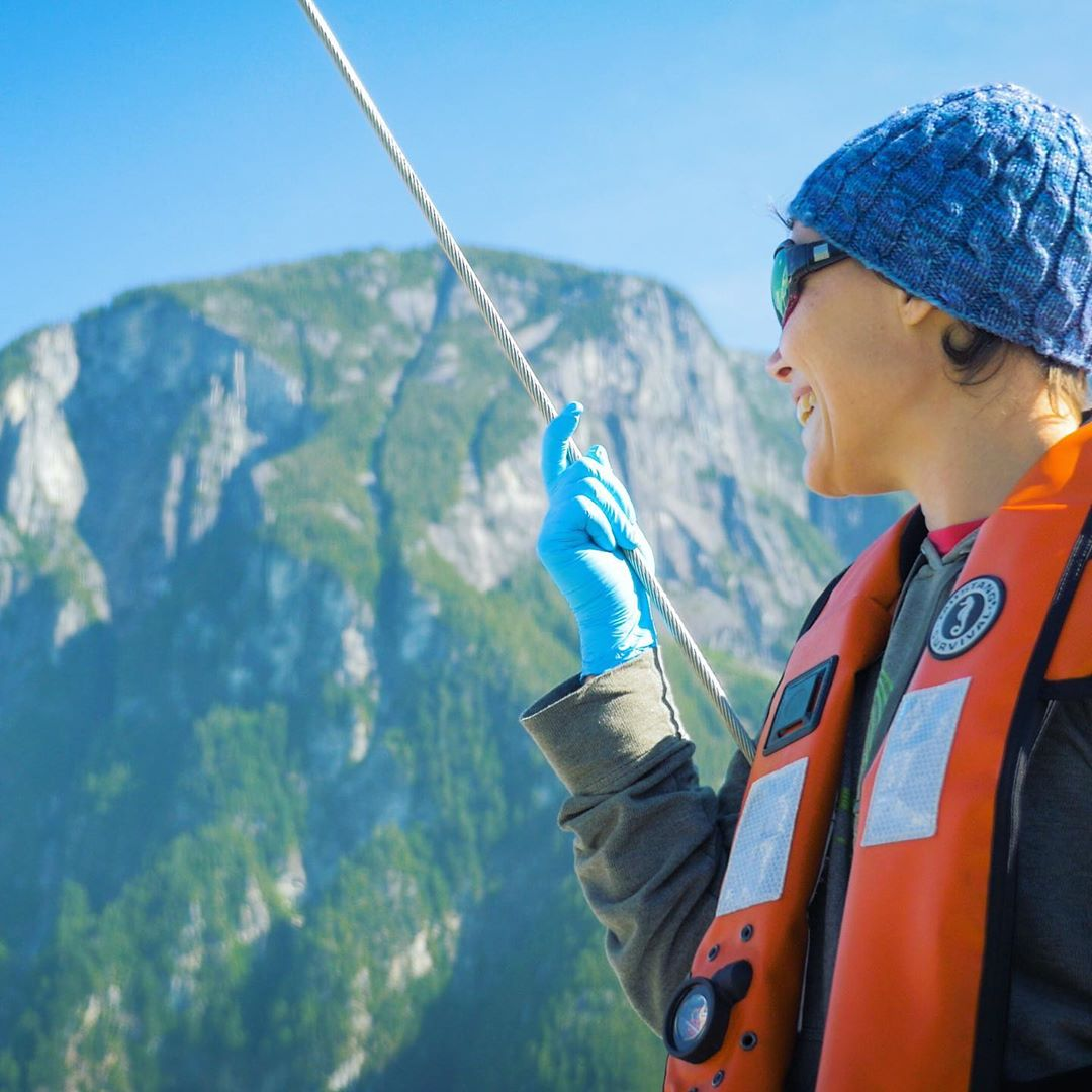 Scientist in blue toque, blue goves and red jacket with a pole in their hand standing on a boat off camera