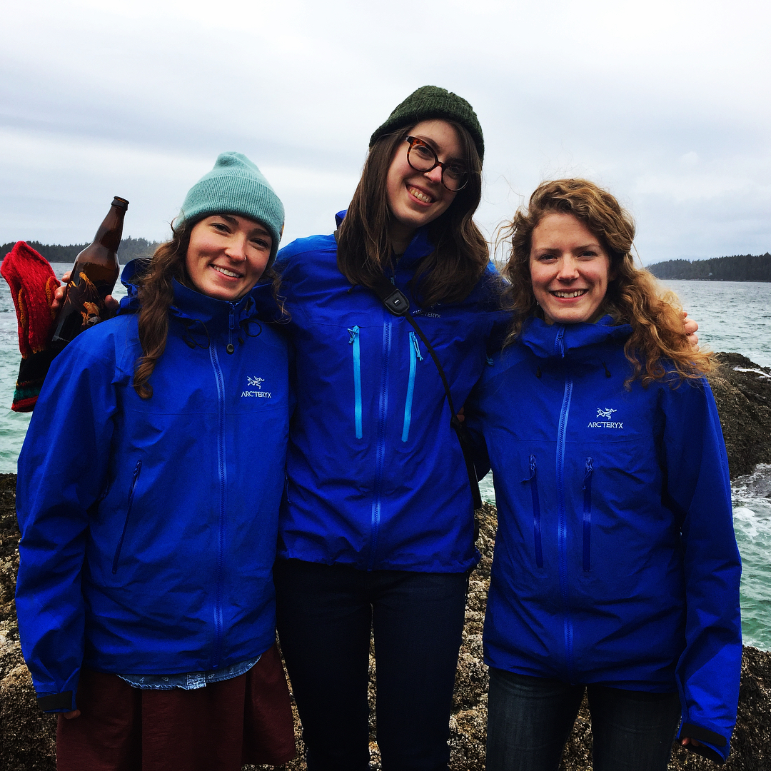 Three scientists in blue rain gear stand with arms around each other besides a boat and the ocean