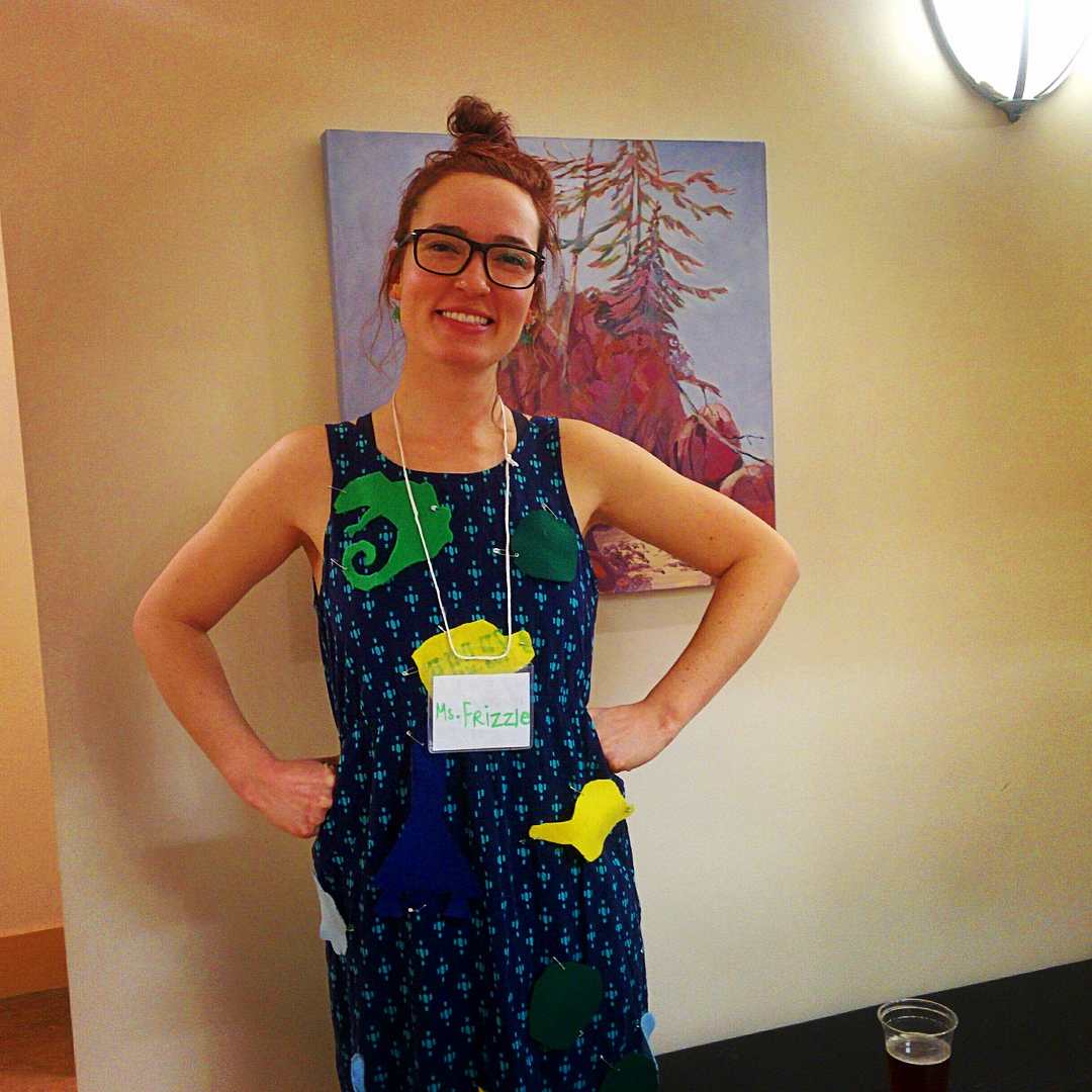 Young woman in black glasses and in a green and black dress poses  before a generic hotel room wall where a print hangs, wearing a conference lanyard.