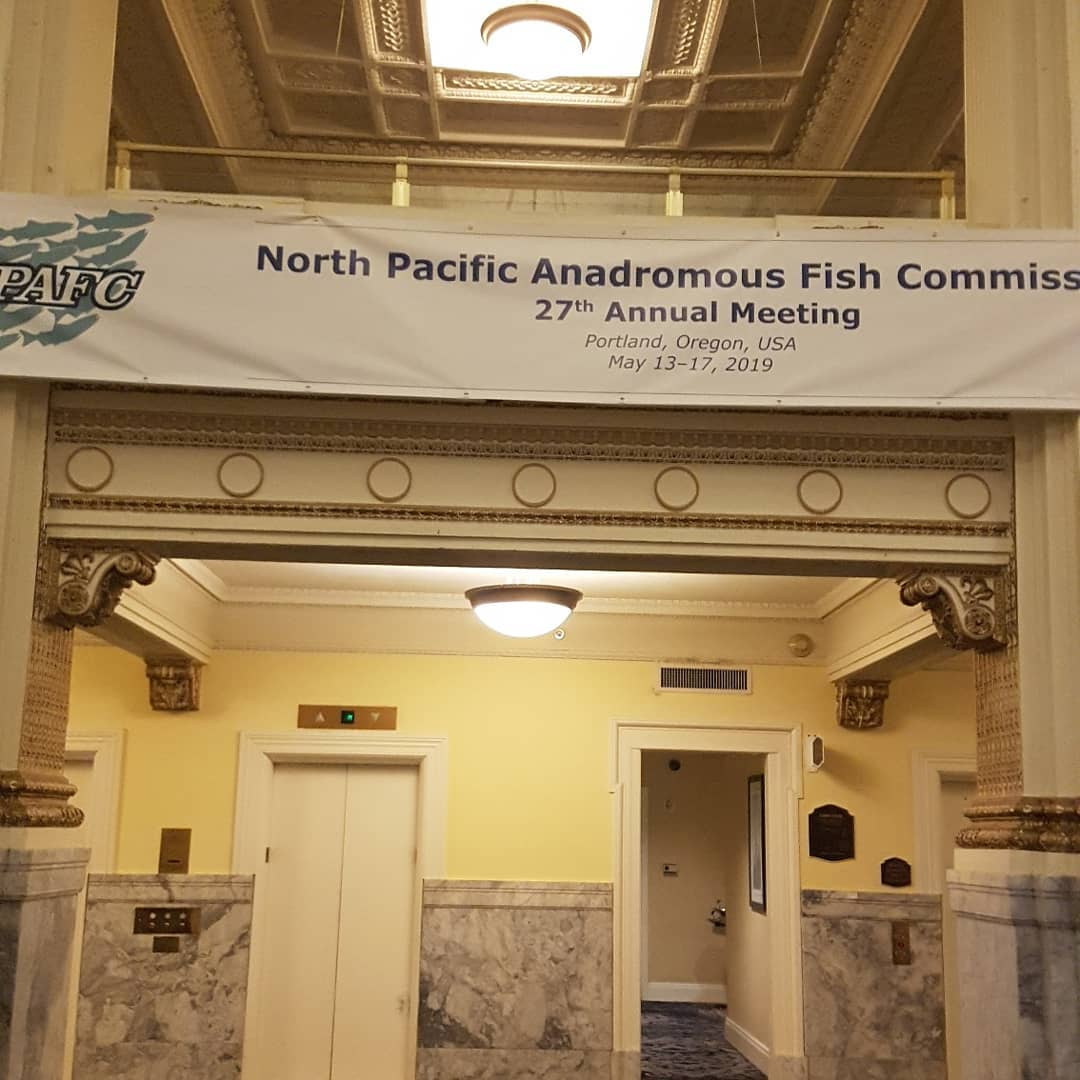 """Hotel lobby with a banner hung across the wall which reads' North Pacific Anadromous Fish Commiss"""""""