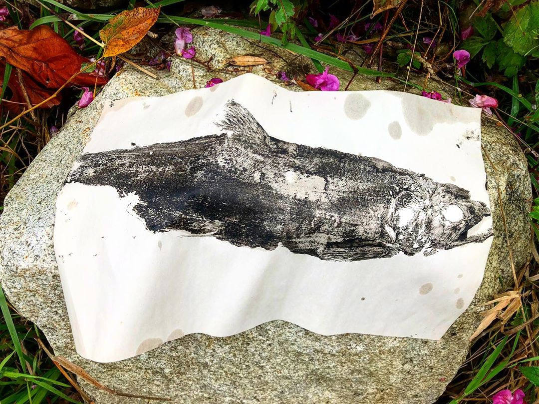 Black and white salmon inkprint on white paper placed on a stone outdoors bordered by some leaves in green and orange
