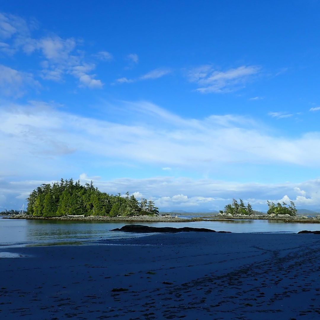 A small island visible amidst dark blue water under blue skies, covered in green