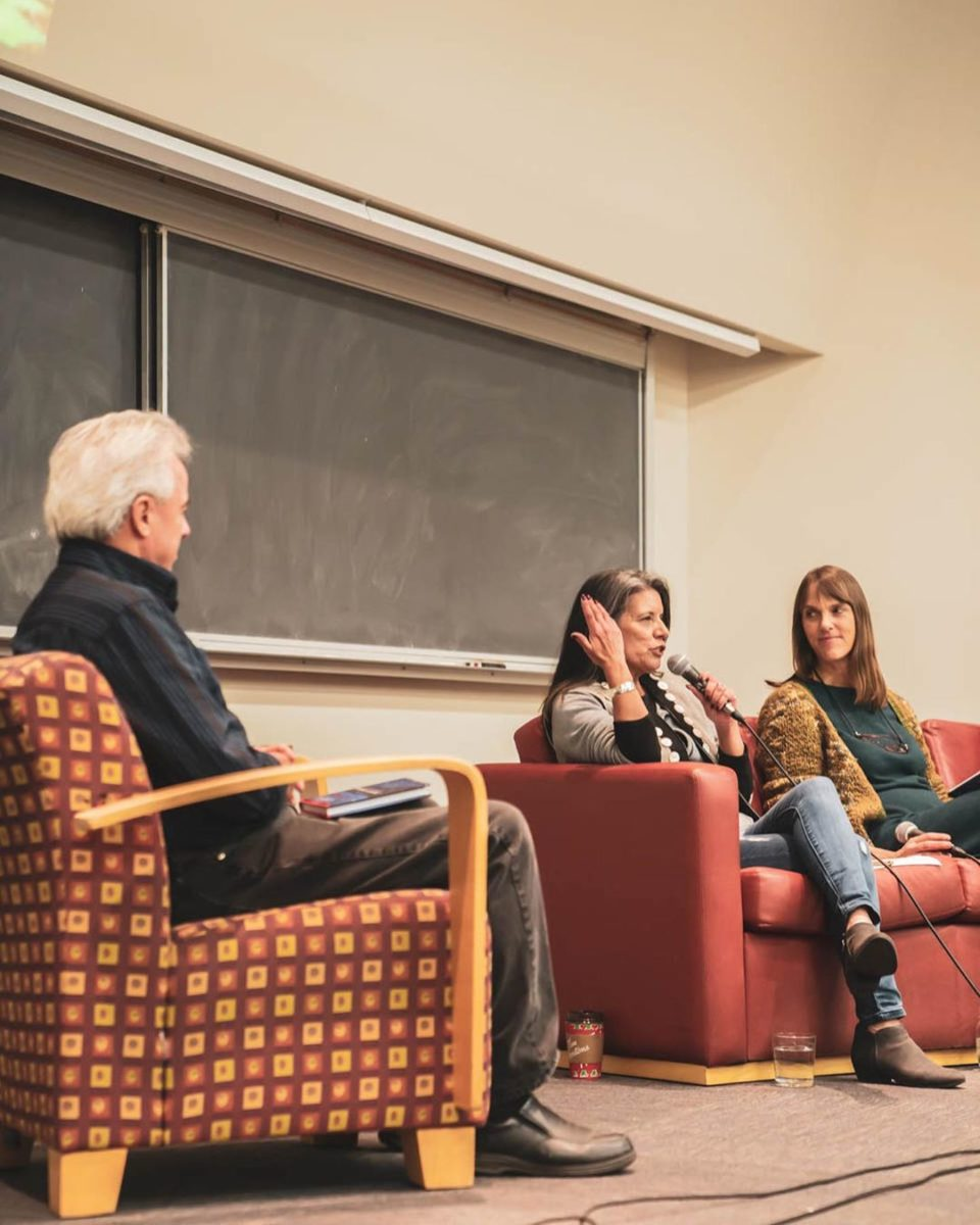 A man sits in a chair facing two other women on a red couch as part of a panel discussion