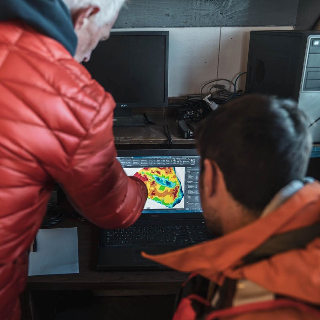 Two scientists in orange jacket point and look at a computer screen showing a colourful map