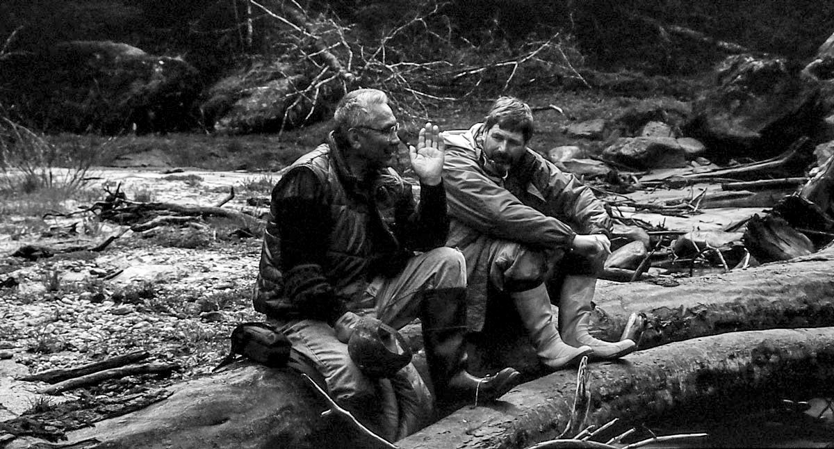 Black and white photograph of Elder Cecil Paul and Brian Falconer as they sit on a log. Brian listens deeply to Elder Cecil Paul while river froths behind them.