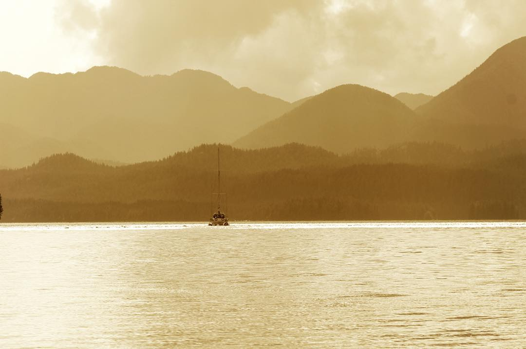 Soft yellow light on ocean and mountains, view is from the deck of Raincoast vessel Achiever, of another boat