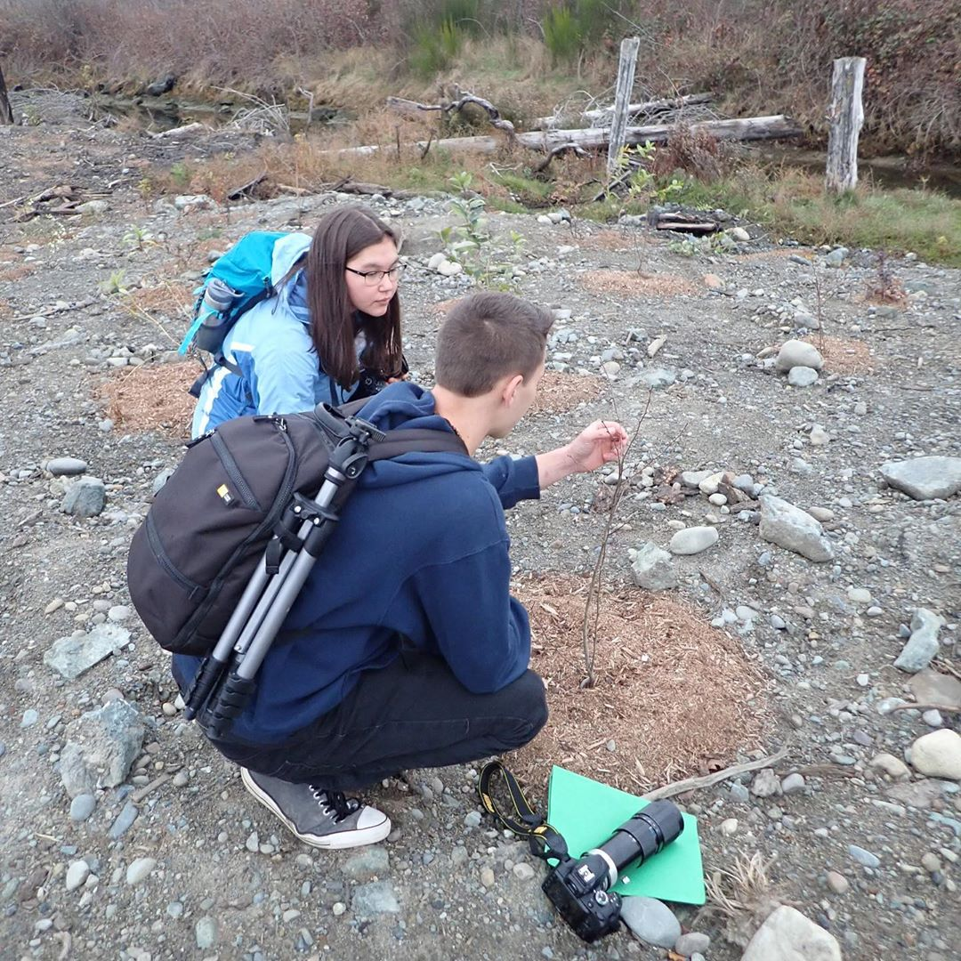 Youth who participate in the Salish Sea Emerging Stewards program crouch over the ground in discussion