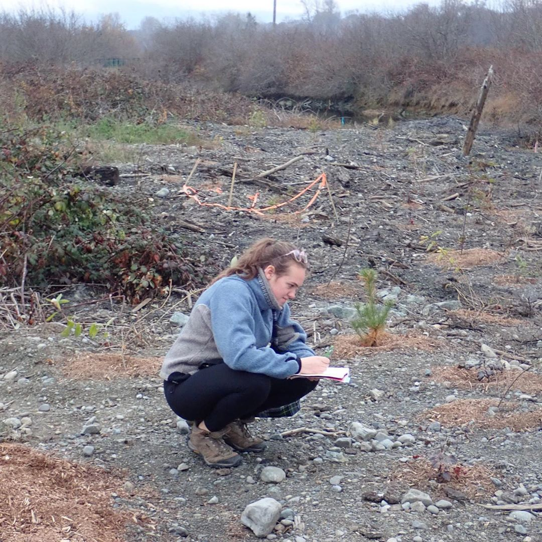 Young person who is part of the Raincoast Foundation's education program squats over a sample and looks it over