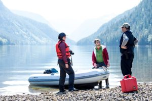 Three Raincoast researchers in life jackets and boots stand on a pebbled shore around a white dinghy speaking to each other while the ocean looms quietly in the background in pale blue, cut by two mountains forming a vee.