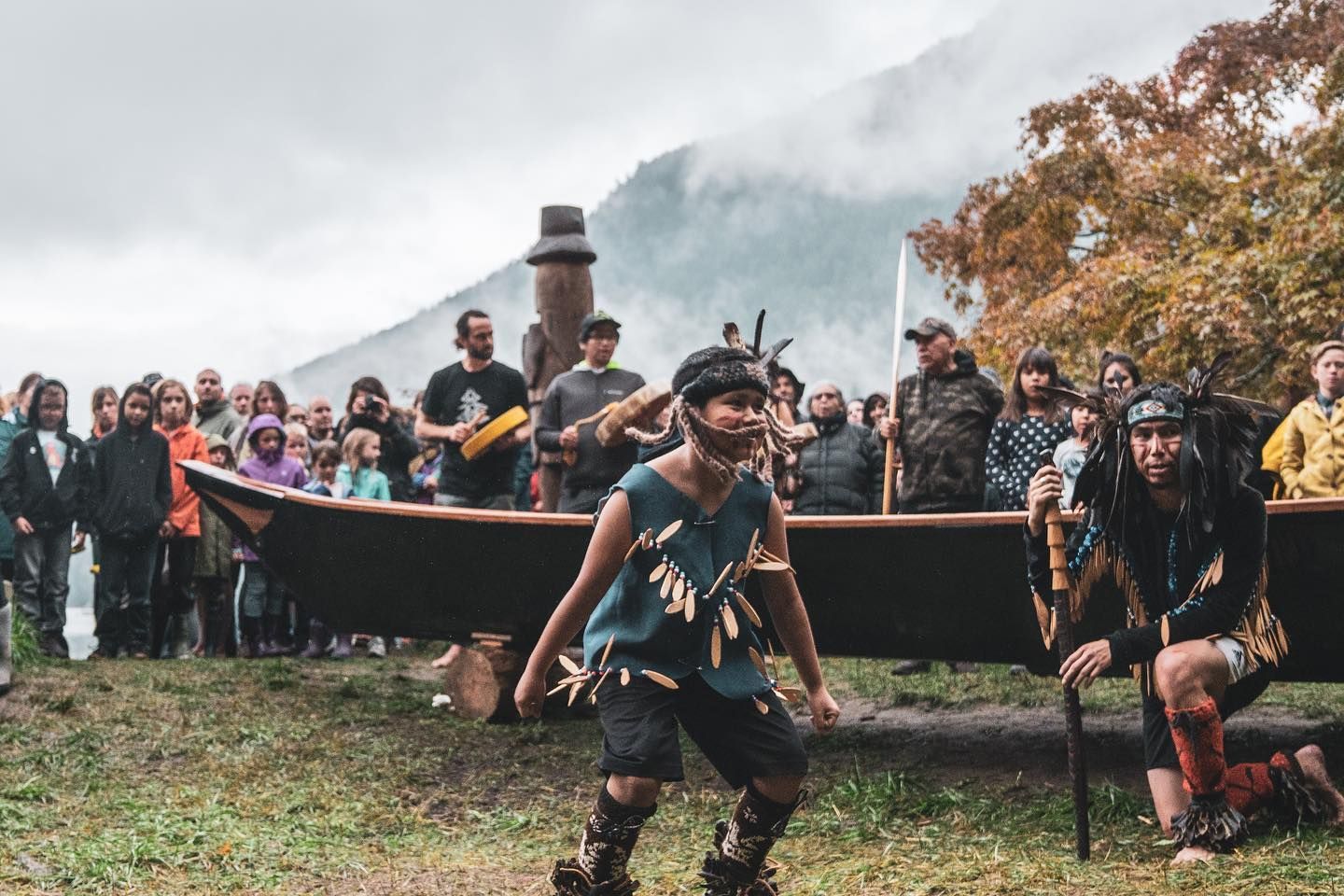Cowichan Nation ceremonial dancer among people watching and misty covered mountain in the background