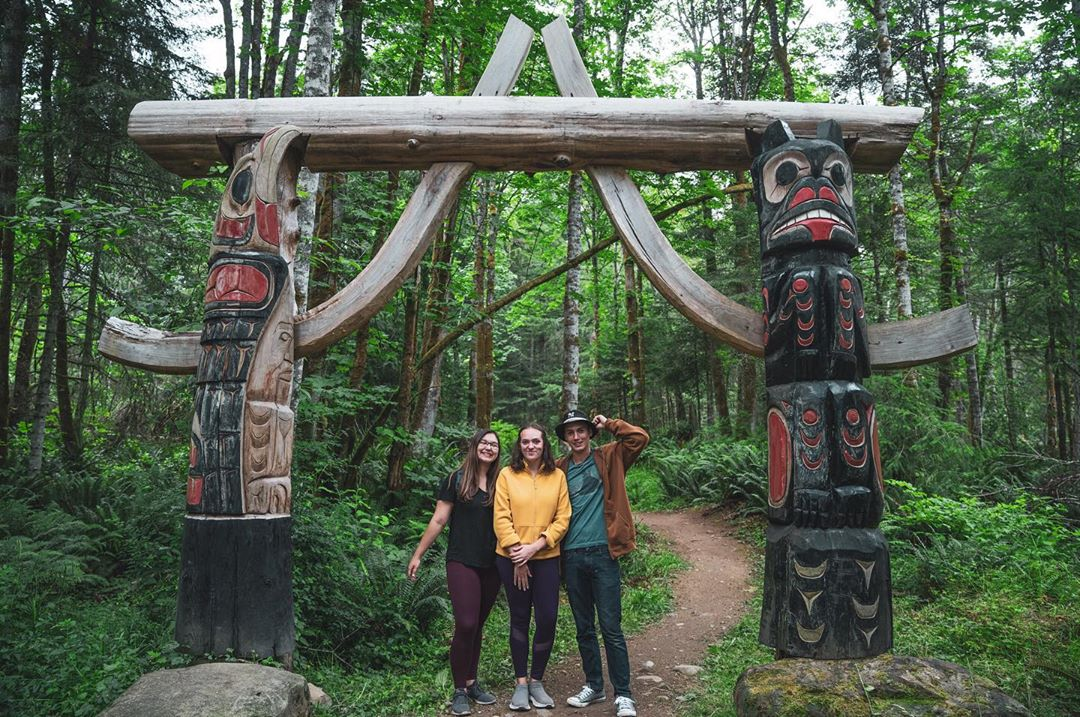 Three youth in colourful clothes yellow, and green and brown stand under a totem arch in a forest.