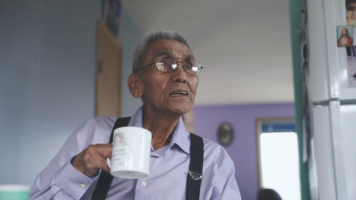 Elder Cecil Paul, wearing glasses, a white shirt and black suspenders seen seated in a room holding a white mug, in conversation.