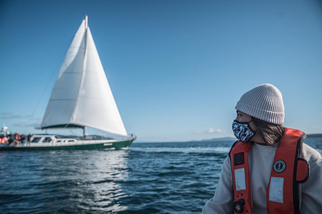 Achiever, sailboat research vessel is seen with white sail unfurled in blue water under bright blue skies, with a youth in winter gear visible partially in the foreground.