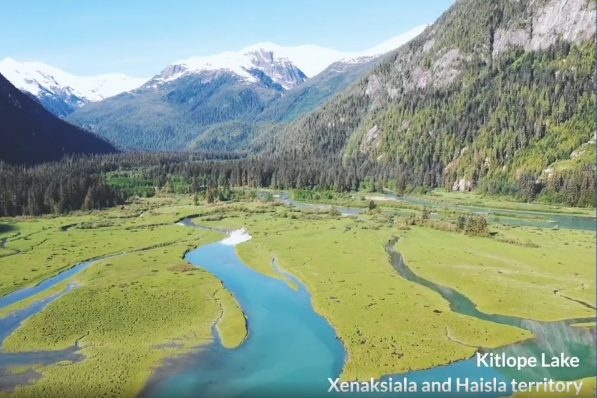 Aerial view of winding blue Kitlope Lake through green banks towards snow capped mountains