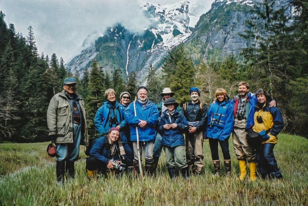 A group of people in blue outdoor gear pose in a arc in the Kitlope valley.