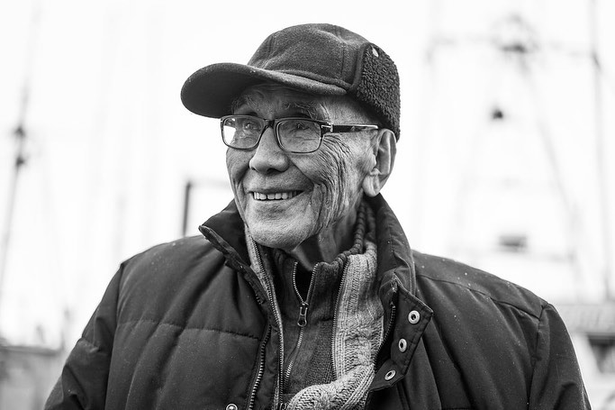 Smiling face of Elder Wa'Xaid captured in a black and white photograph. He is wearing a cap, glasses and a jacket.