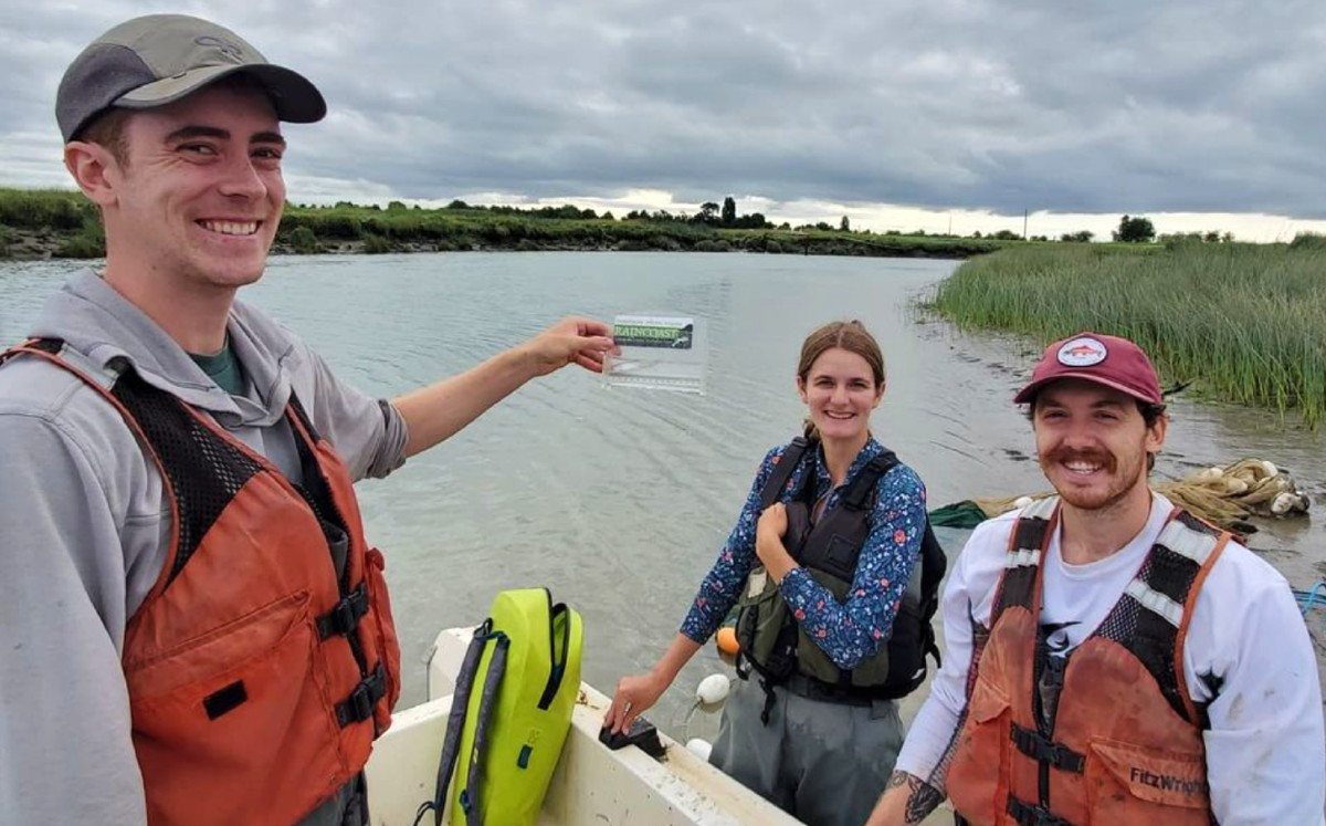 Three crew members smile posing with a tiny Chinook fry in a measuring device with the river stretching out behind them.