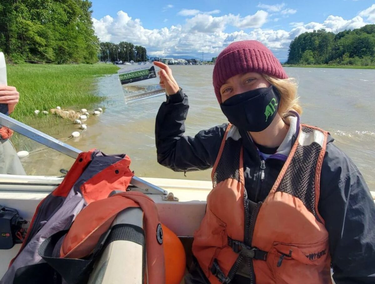 A field crew member sits in the boat on the Fraser River and smiles through their COVID mask.
